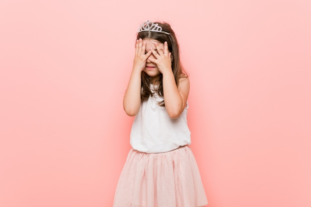 Mała dziewczynka w wyglądzie księżniczki mruga przez palce przestraszona i nerwowa