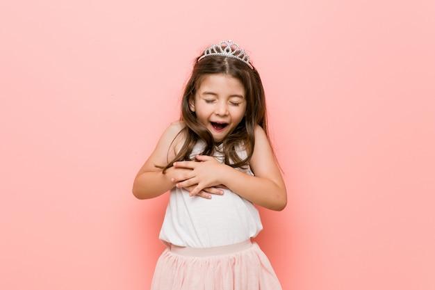 Mała dziewczynka w wyglądzie księżniczki śmieje się radośnie i dobrze się trzyma, trzymając ręce na brzuchu.
