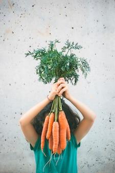 Mała dziewczynka w zielonej koszuli zasłaniając twarz niektórymi domowymi marchewkami