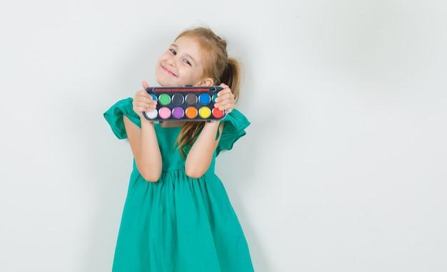 Mała dziewczynka w zielonej sukience trzymając farby akwarelowe z pędzelkiem i patrząc wesoło