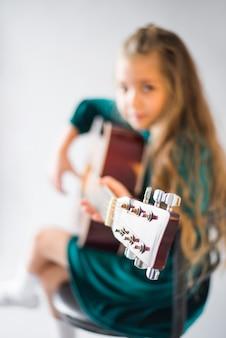 Mała dziewczynka w zielonej sukni bawić się gitarę akustyczną