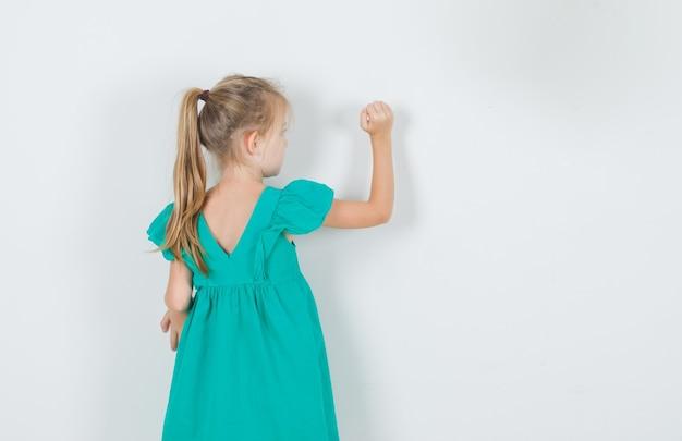 Mała dziewczynka w zielonej sukni, patrząc na ścianę, widok z tyłu.