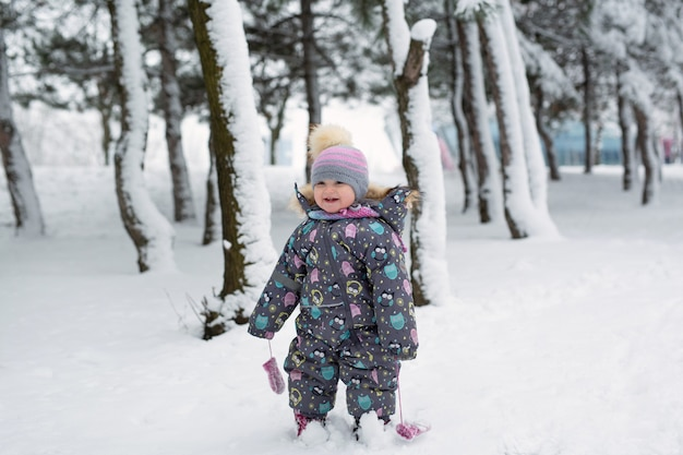 Mała dziewczynka w zimie w zaśnieżonym lesie.