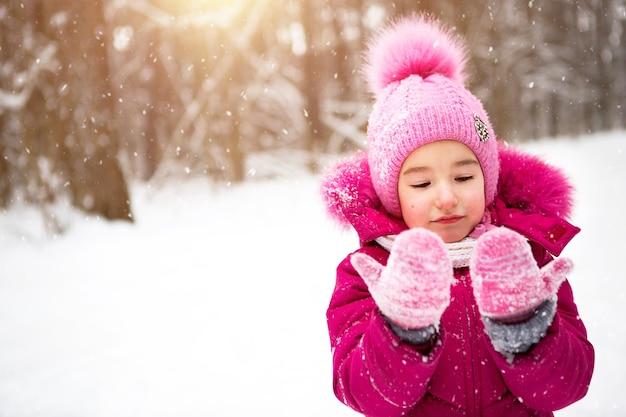Mała dziewczynka w zimnie patrzy na śnieżne rękawiczki i uśmiecha się