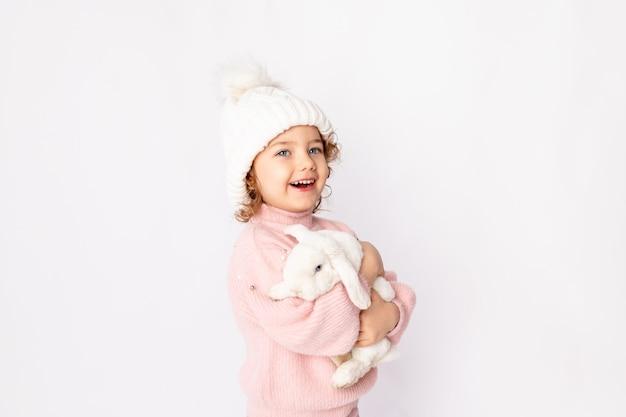 Mała dziewczynka w zimowe ubrania trzyma królika na białym tle.