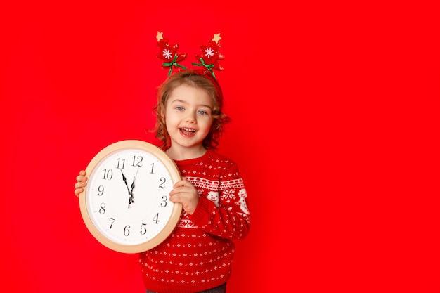 Mała dziewczynka w zimowe ubrania trzyma zegarek na czerwonym tle. koncepcja nowego roku, miejsce na tekst