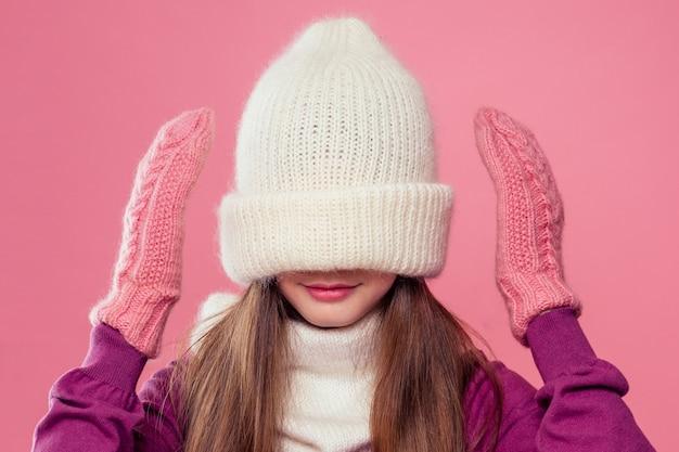 Mała dziewczynka w zimowym ciepłym białym kapeluszu i szaliku oraz w różowych rękawiczkach marzy noc bożego narodzenia bawiąc się w chowanego w studio na różowym tle. fotografia portretowa model dziecka ukrywający oczy pod czapką