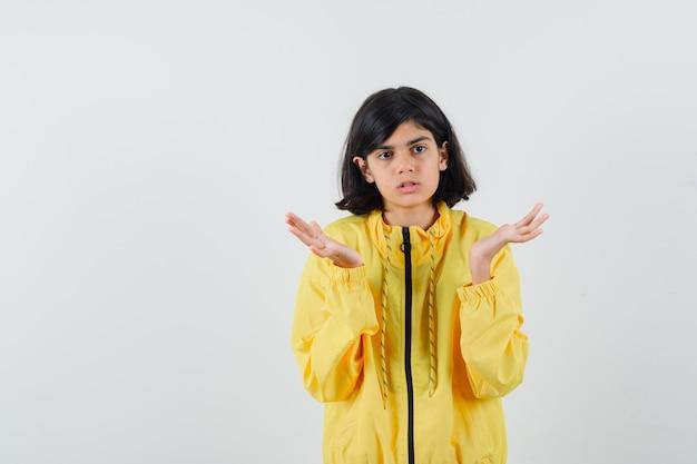 Mała dziewczynka w żółtej bluzie z kapturem, pokazująca bezradny gest i wyglądająca na zdezorientowaną, widok z przodu.