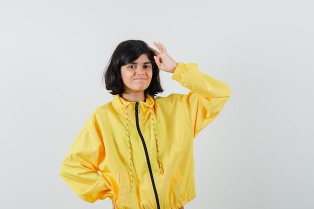 Mała dziewczynka w żółtej bluzie z kapturem pokazująca gest salutowania i wyglądająca dumnie, widok z przodu.