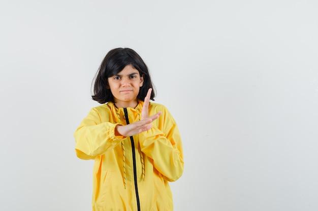 Mała dziewczynka w żółtej bluzie z kapturem pokazuje gest karate chop i wygląda pewnie, widok z przodu.