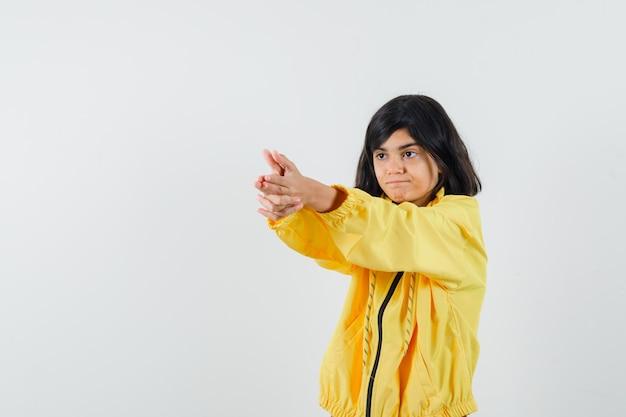 Mała dziewczynka w żółtej bluzie z kapturem pokazuje gest pistoletu i wygląda pewnie, widok z przodu.