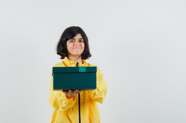 Mała dziewczynka w żółtej bluzie z kapturem prezentująca pudełko i wyglądająca wesoło, widok z przodu.