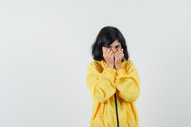 Mała dziewczynka w żółtej bluzie z kapturem, trzymając się za ręce na twarzy i patrząc przestraszony, widok z przodu.