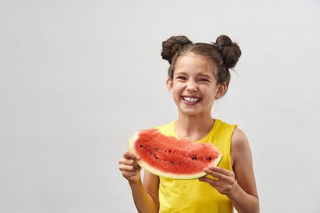 Mała dziewczynka w żółtej koszulce, śmiejąc się wesoło i trzymając kawałek arbuza
