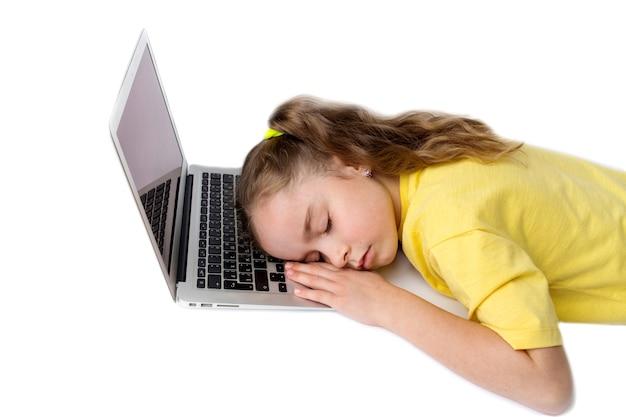 Mała dziewczynka w żółtej koszulce zmęczyła się i zasnęła przy laptopie. pojęcie nauczania na odległość podczas covid-19. zdjęcie wysokiej jakości