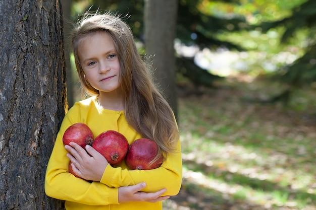 Mała dziewczynka w żółtej kurtce stoi w parku i trzyma dojrzałe granaty.