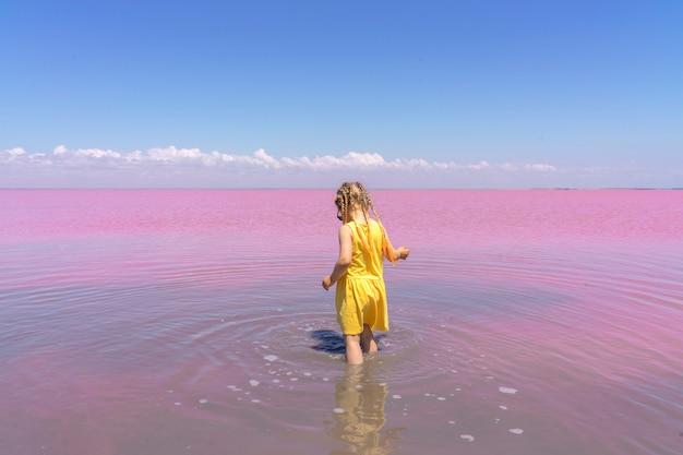 Mała dziewczynka w żółtej sukience spaceruje wzdłuż wybrzeża różowego jeziora