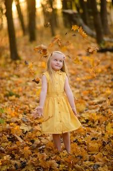 Mała dziewczynka w żółtej sukience w jesiennym parku. dziecko rzuca liście.