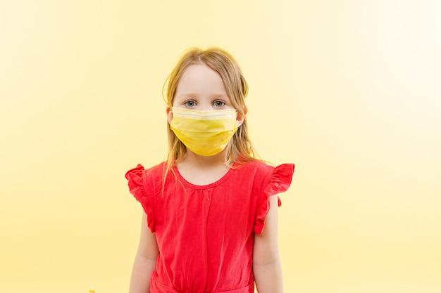 Mała dziewczynka w żółtej twarzy masce. zatrzymaj koncepcję wirusów.