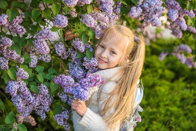 Mała dziewczynka wącha bzu kwitnie w słonecznym dniu.