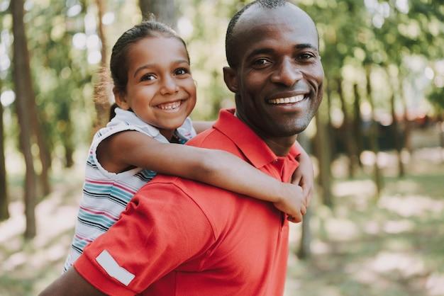 Mała dziewczynka wisi ojciec za plecami.
