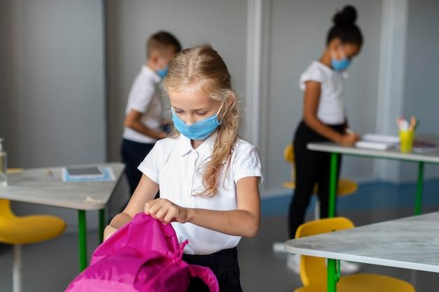 Mała dziewczynka wkłada książki do plecaka