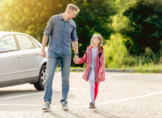 Mała dziewczynka wraca do szkoły, trzymając się za ręce z ojcem