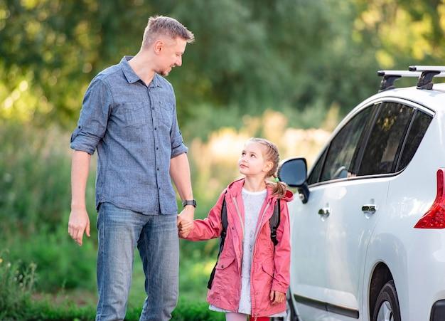 Mała dziewczynka wraca do szkoły trzymając się za ręce z ojcem