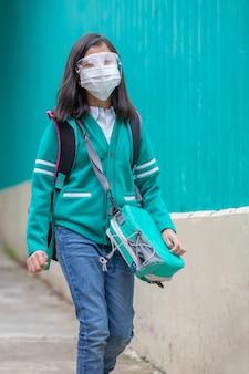 Mała dziewczynka wraca do szkoły w plastikowej masce na twarz po pandemii koronawirusa, pionowe ujęcie