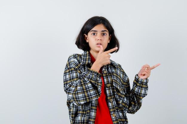 Mała dziewczynka, wskazując na bok w koszuli, widok z przodu kurtki.