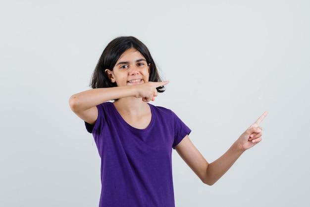 Mała dziewczynka, wskazując na bok w t-shirt i patrząc wesoło