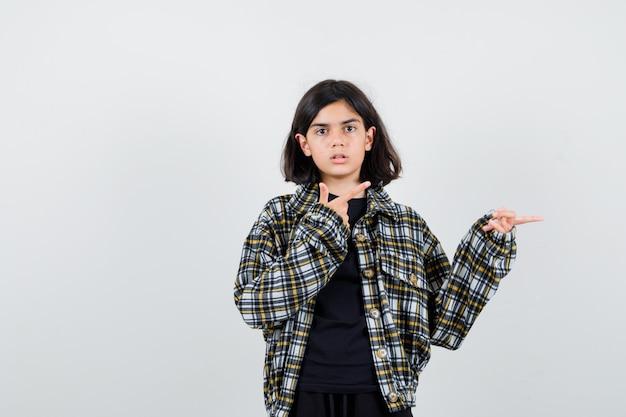 Mała dziewczynka wskazując na prawą stronę w t-shirt, kurtkę i wyglądający pewnie. przedni widok.