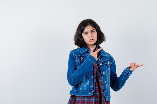 Mała dziewczynka, wskazując na prawy górny róg w koszuli, kurtce i patrząc niezdecydowany, widok z przodu.