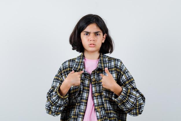Mała dziewczynka, wskazując na siebie w koszuli, kurtce, widok z przodu.