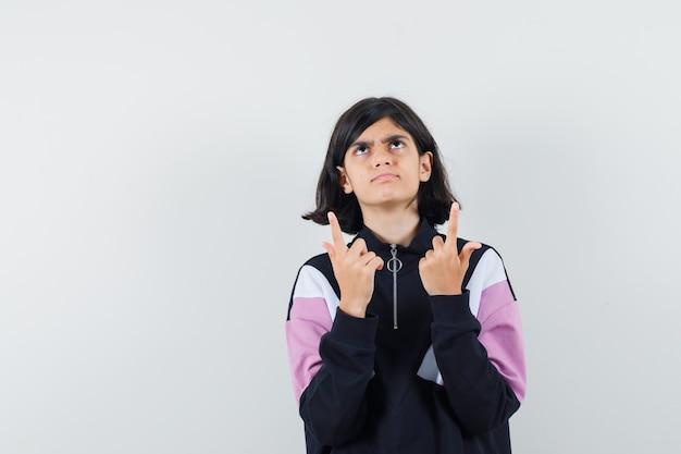 Mała dziewczynka wskazując palcami w koszuli i patrząc wątpliwie. przedni widok.