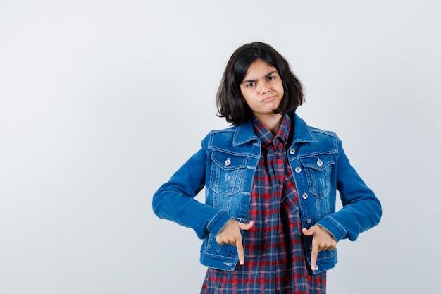 Mała dziewczynka wskazując w dół w koszulę, kurtkę i patrząc niezdecydowany. przedni widok.