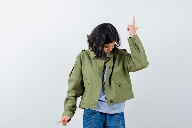 Mała dziewczynka wskazując w górę iw dół w płaszczu, koszulce, dżinsach i patrząc niezdecydowany, widok z przodu.