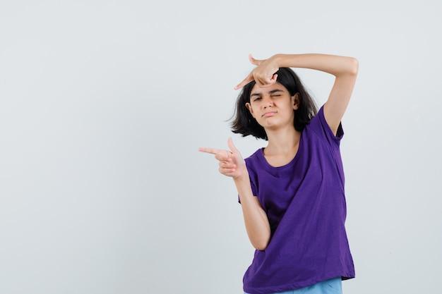 Mała dziewczynka wskazująca na lewą stronę w t-shircie i wyglądająca na pewną siebie.