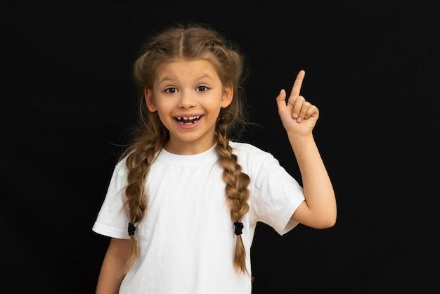Mała dziewczynka wskazuje na twoją reklamę na czarnym tle.