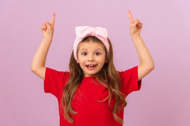 Mała dziewczynka wskazuje obiema rękami na fioletowym tle