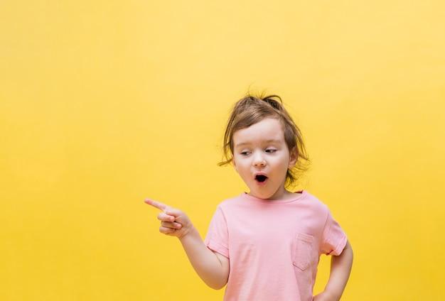 Mała dziewczynka wskazuje palcem bok na żółtym polu. ładna dziewczyna zaskoczona kucykiem w różowej koszulce. skopiuj miejsce