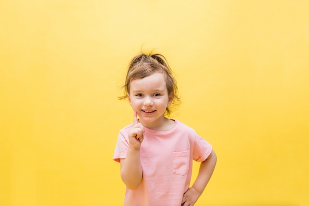 Mała dziewczynka wskazuje palcem na żółtym polu. śliczna dziewczyna z kucykiem w różowej koszulce. skopiuj miejsce