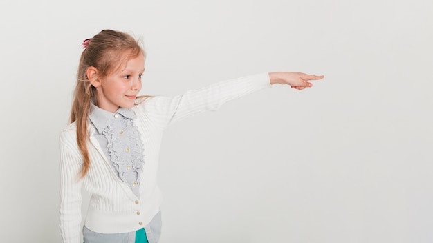 Mała dziewczynka wskazuje w kierunku copyspace