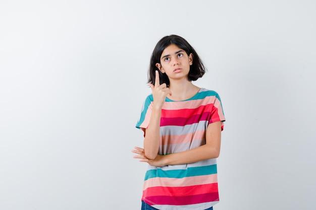 Mała dziewczynka wskazuje w t-shirt i patrząc zamyślony, widok z przodu.