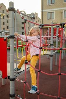 Mała dziewczynka wspina się po linie na placu zabaw na tle domów w lecie