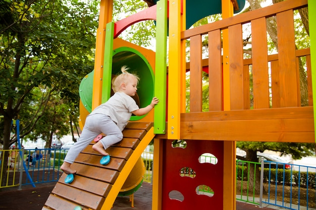 Mała dziewczynka wspina się po ścianie wspinaczkowej na zjeżdżalni dla dzieci na placu zabaw.