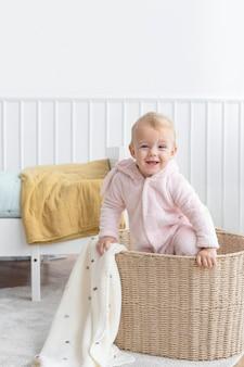Mała dziewczynka wspina się w koszu na pranie