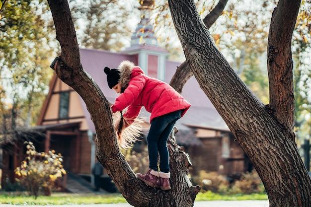 Mała dziewczynka wspinać się na drzewo
