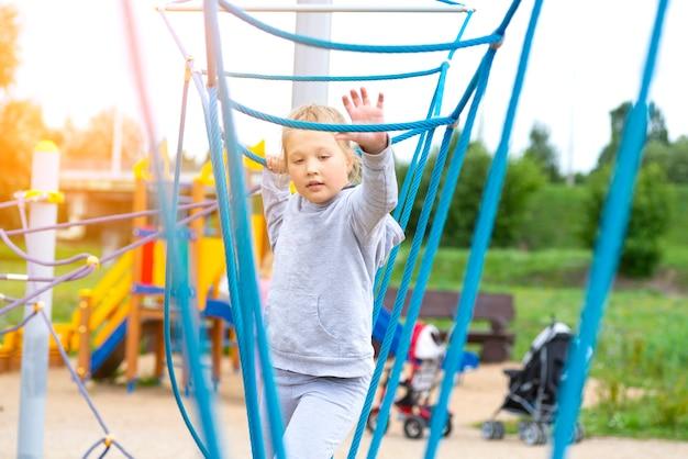 Mała dziewczynka wspinaczka w parku rozrywki. dziewczyna uwielbia wspinać się w przygodzie na park linowy. mała dziewczynka na torze przeszkód linowych.