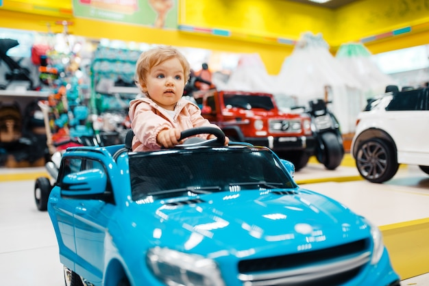 Mała dziewczynka wybiera elektromobilny w sklepie dla dzieci, widok z przodu
